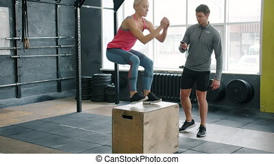 Sportswoman is jumping on box focused on aerobic exercise while coach is checking time with timer smiling talking. Instructor, people and indoors sports concept.