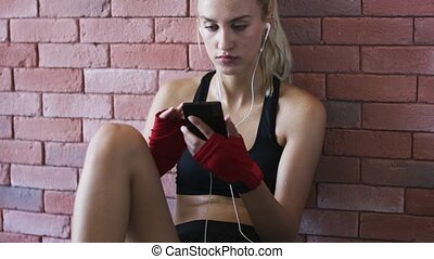 Sportswoman listening to music and using smartphone - Pretty...