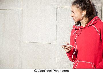 Sportswoman listening to music using phone app