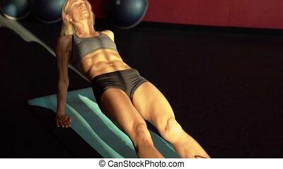 Sportswoman on exercise mat doing abdominal exercise....