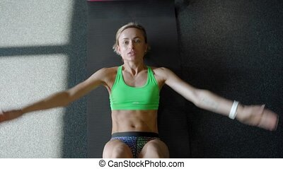Sportswoman on exercise mat doing abs workout in gym. Muscular female athlete doing abs workout.