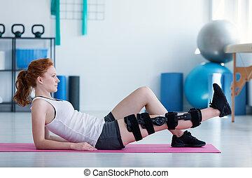 Sportswoman on mat doing exercises with broken leg during rehabilitation