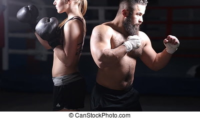 Sportswoman on sparring with her kickboxing instructor. Man and a woman in the Boxing ring