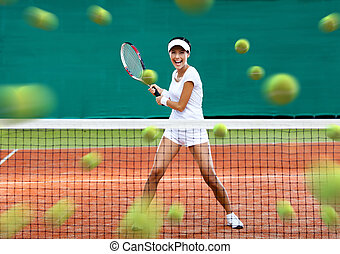 Sports woman returning lots of balls at the tennis court. Concept of tournament preparation and healthy lifestyle
