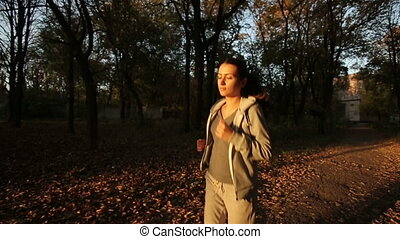 Sportswoman Runs In autumn park