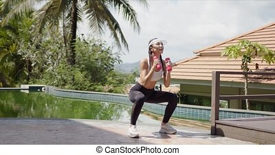 Full length fit lady in sportswear performing squats with dumbbells near swimming pool during fitness workout on sunny day on resort
