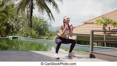 Sportswoman squatting with dumbbells on poolside - Full ...