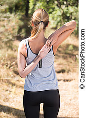 sportswoman stretching arm in the forest