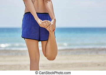 Sportswoman stretching her legs on beach