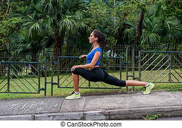 Sportswoman stretching in leg lunge position with tropical park in the background. Fit girl exercising outdoors.