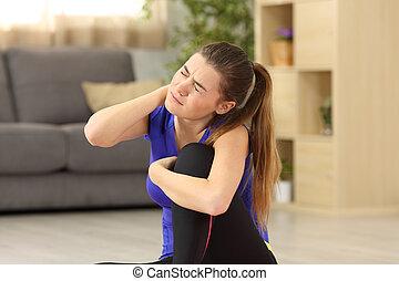 Sportswoman suffering neck ache at home - Sportswoman...