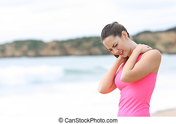 Sportswoman suffering neck ache on the beach