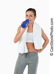 Sportswoman taking a sip out of her bottle