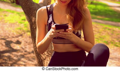 sportswoman texting message on mobile outdoors