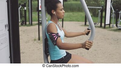 Sportswoman training in park - Side view of young serious...