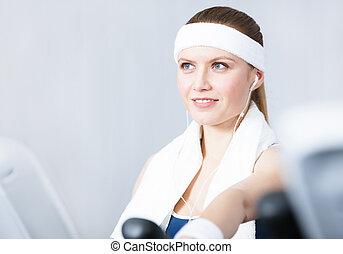 Sportswoman training on gym equipment in gym