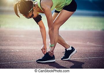 Sportswoman tying shoelace before run on stadium