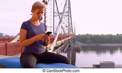 sportswoman use app on mobile - young caucasian woman with...
