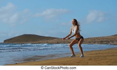 Sportswoman Wearing Sportswear Doing Squats Exercise Outdoors. Fitness Female Working Out on the Beach at Sunset. Athletic Young Woman is Engaged in Outdoor Sports.