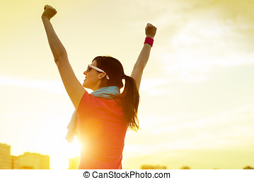 Sportswoman with arms up celebrating success - Happy...