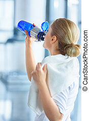 sportswoman with towel drinking water from sport bottle in sports center