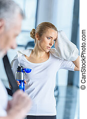 sportswoman with towel holding sport bottle in sports center