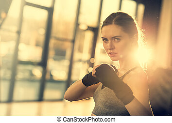 sportswoman with wraping hands ready to fight in sports center