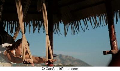 Sportswoman Woman doing yoga exercise on tissue bandage...