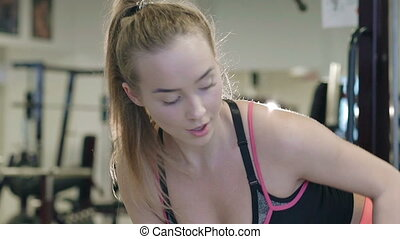 Sportswoman working out lifting dumbbells in pose at the gym. Slowly