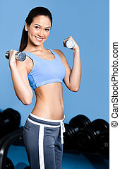 Sportswoman works out with dumbbells