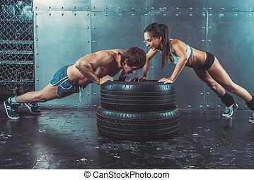 sportswomen., ajustar, sporty, mulher homem, fazendo, empurrão, ups, ligado, pneu, força, poder, treinamento, conceito, crossfit, condicão física, malhação, desporto, lifestyle.