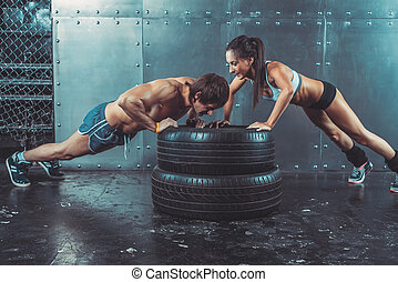 Sportswomen. Fit sporty woman and man doing push ups on tire...