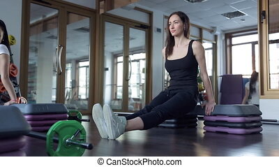Sportswomen pick up the body, relying on the sports platform hands.