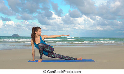 Sporty active woman practicing yoga on the beach at sunset. Healthy lifestyle.