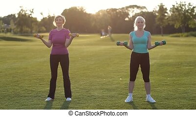 Sporty adult women with dumbbells flexing muscles