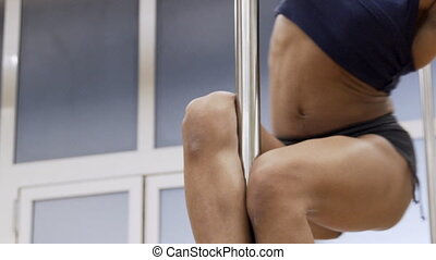 Sporty African American female body is slowly spinning on metal pole.