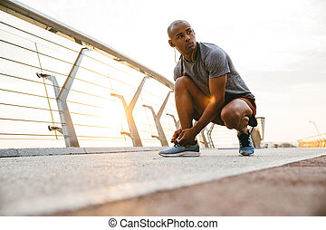 Sporty african man tying shoelace on bridge
