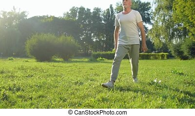 Sporty aged man doing lungs exercises in the park