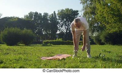 Sporty aged man doing warm up exercises outdoors