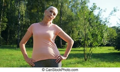 Sporty aged woman doing morning exercises outdoors