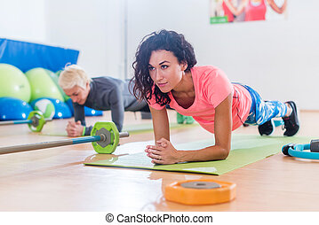 Sporty attractive young females doing yoga forearm planking exercise or Dolphin pose on mats while training in fitness club