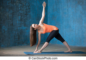 Sporty attractive young woman Doing Parivrrta Trikonasana pose