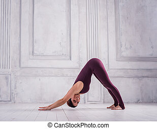 Sporty attractive young woman practicing yoga, standing in Downward facing dog exercise, adho mukha svanasana pose. Sporty young woman doing yoga practice on light background.