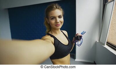 Sporty beautiful long hair blonde girl with jump rope making...