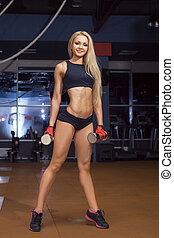 Sporty beautiful woman stands in the gym. Fitness.