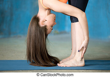 Sporty beautiful young woman Doing Standing forward bend pose