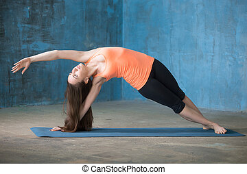 Sporty beautiful young woman doing Vasisthasana pose