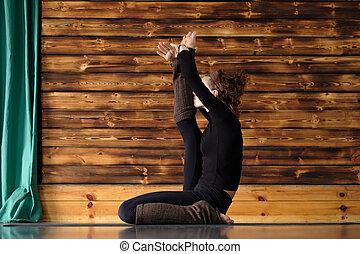 beautiful curly woman doing yoga excercise bhujapidasana