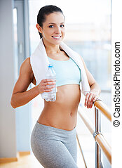 Sporty beauty. Attractive young woman in sports clothing holding bottle with water and smiling while standing in health club