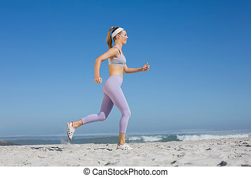 Sporty blonde on the beach jogging